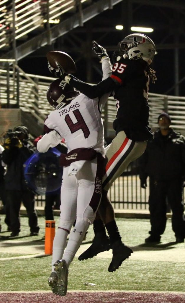 Union receiver C.J. Moore goes up over Jenks defensive back Braden Phipps for a touchdown Friday in the Redskins' 45-21 Class 6A-1 semifinal victory over the Trojans. (PHOTO: John E. Hoover)
