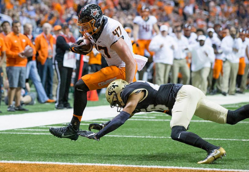Blake Jarwin hurdles over Colorado's Isaiah Oliver for a touchdown in OSU's 38-8 victory Thursday in the Alamo Bowl. (PHOTO: Bruce Waterfield/OSU media relations)