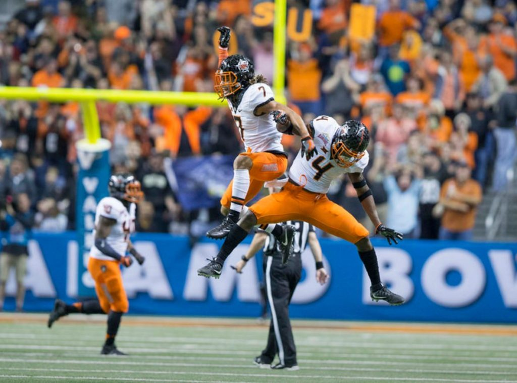 Oklahoma State defensive backs Ramon Richards (7) and Lenzy Pipkins celebrate a stop in the Cowboys' 38-8 victory over Colorado on Thursday night at the Alamo Bowl in San Antonio. (PHOTO: Bruce Waterfield/OSU media relations)